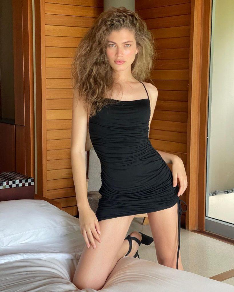 Valentina Sampaio in a black dress on a bed