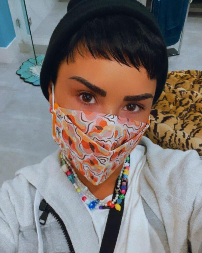 Demi Lovato taking a selfie in a facemask