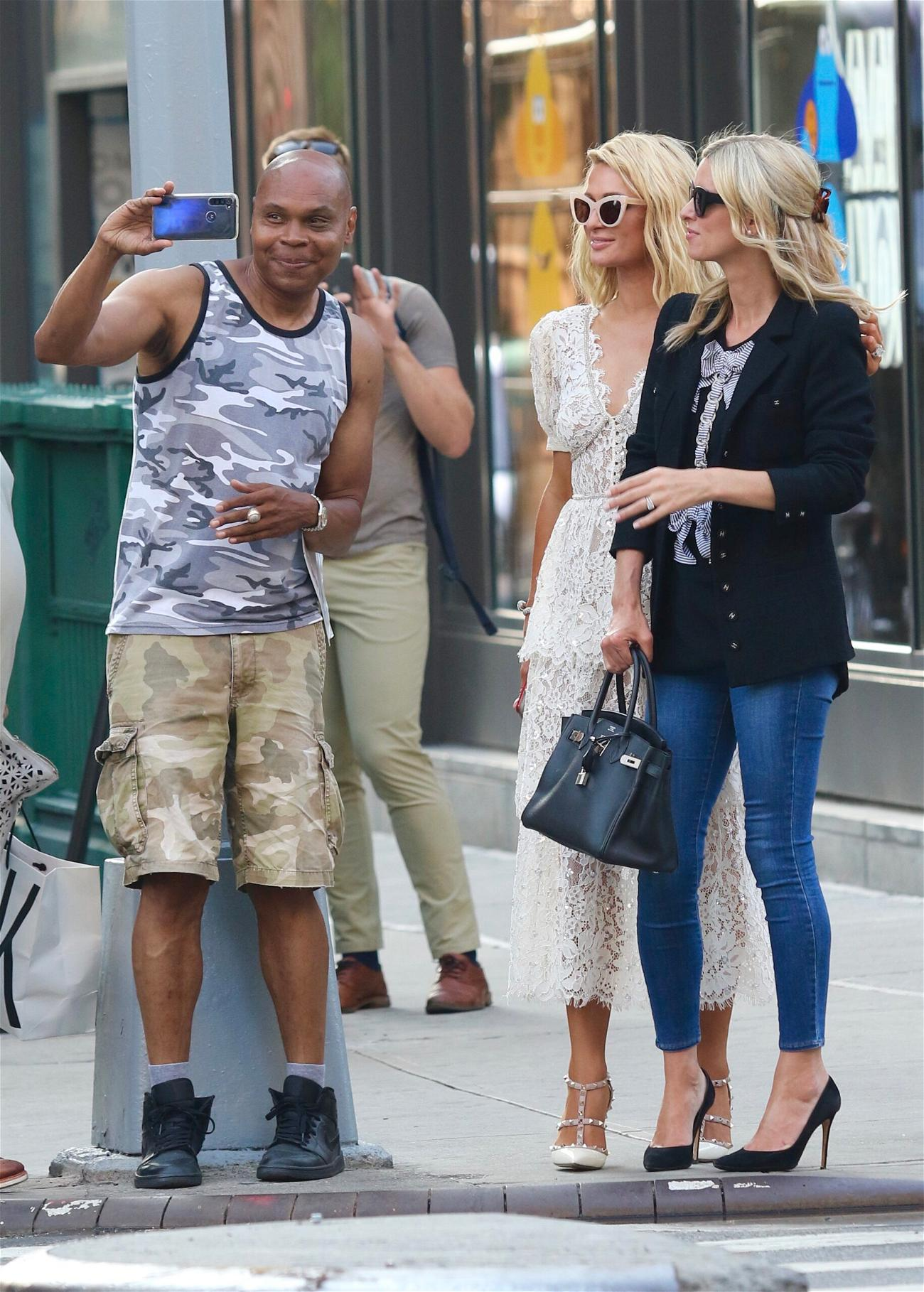 Paris and Nicky Hilton pose with fans.