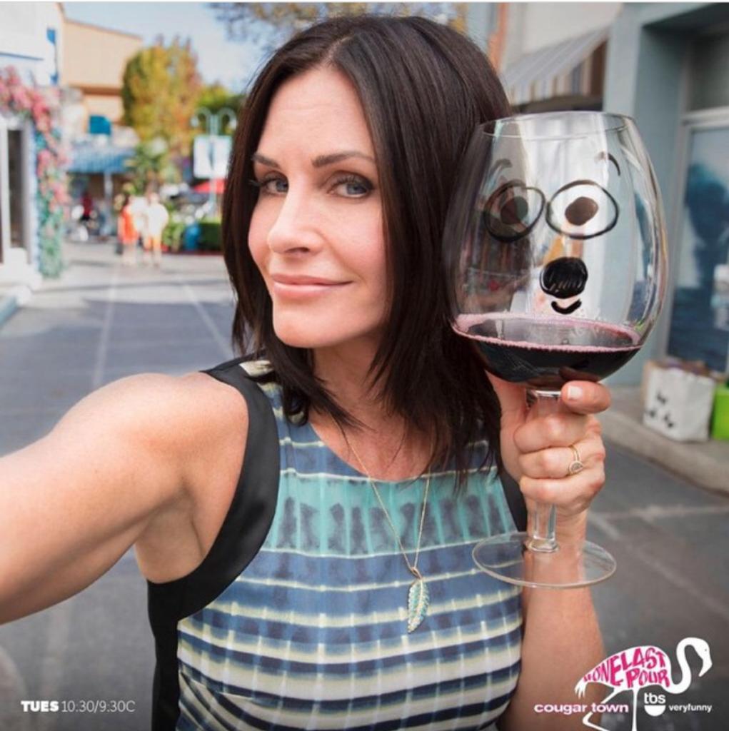 Courteney Cox with wine in her hand