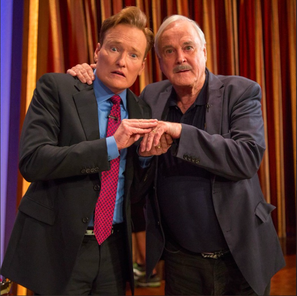 Conan O'Brien and John Cleese holding hands