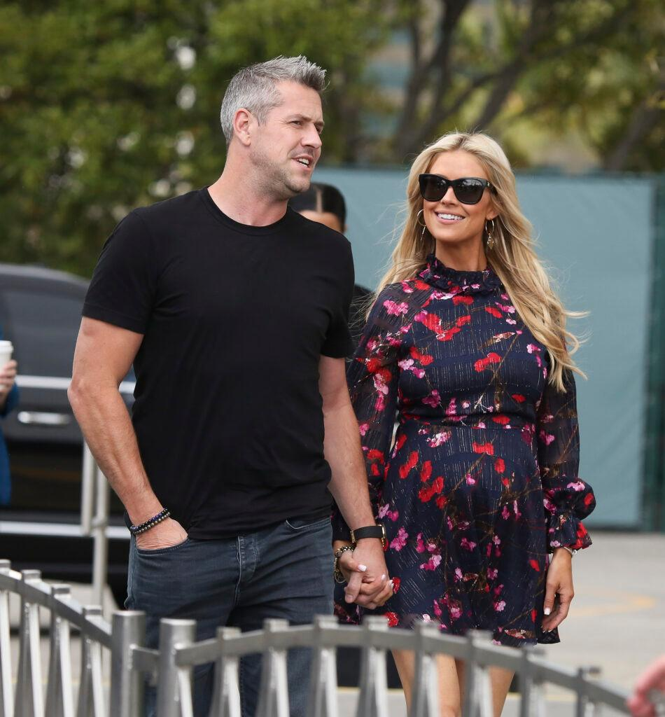 Pregnant Christina Anstead and her husband Ant holding hands while arriving on apos Extra apos
