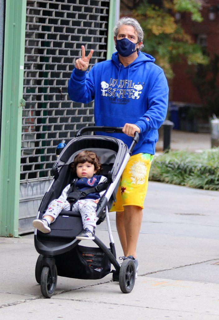 Andy Cohen gives the peace sign and a thumbs up while on a stroll with his son Benjamin in NYC
