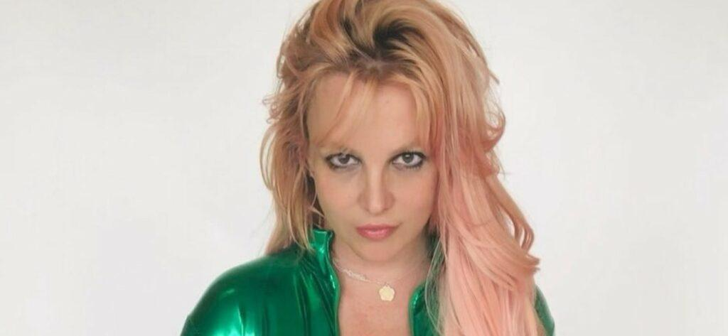 Britney Spears wearing a shiny green body suit.