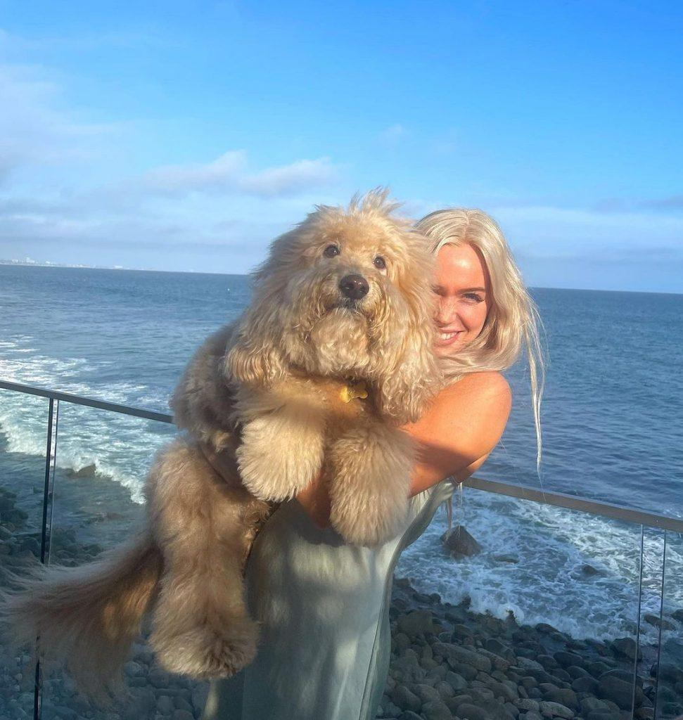Alex Cooper holding a dog in front of the ocean