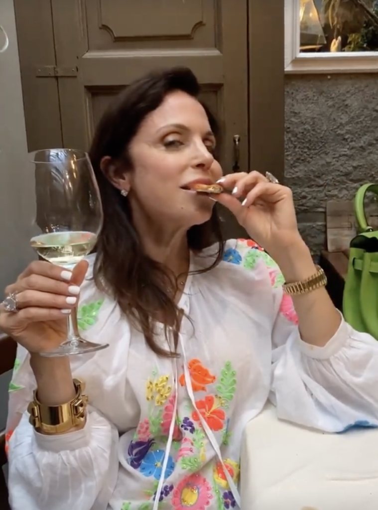 Bethenny Frankel eating pizza and drinking wine
