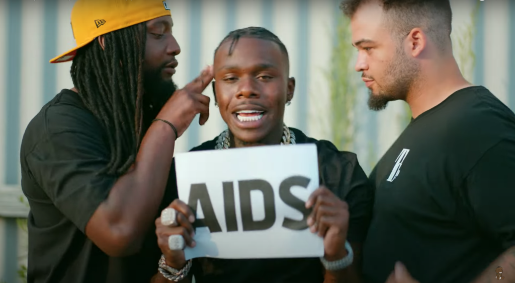 DaBaby holding up a sign that says AIDS