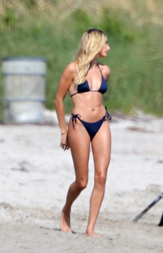 Hailey Bieber wears a black bikini as she poses during a photoshoot on the beach in Miami