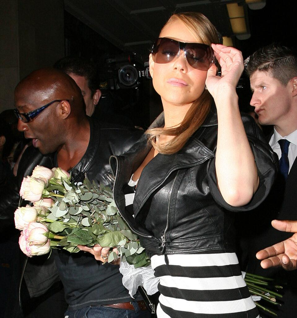 Mariah Carey is greeted by over 30 photographers and fans as she arrives at her London hotel just after 2 30am The singer wore a black and white striped dress black boots leggings a black leather jacket and carried a large bouquet of pink roses