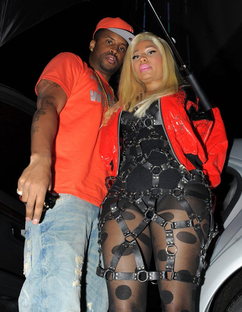 Nicki Minaj and her boyfriend Safaree Samuels arriving back to their hotel Security attempted to block people taking pictures of them with umbrellas Nicki was wearing a dress made from leather belts and a red jacket