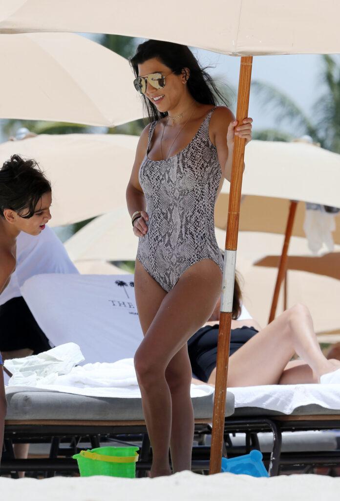 Kourtney Kardashian shows off her amazing beach body in a snakeskin print one piece swimsuit in Miami