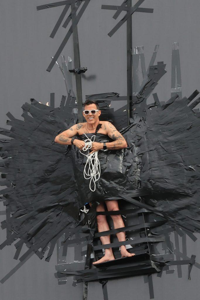 Steve O is helped down by emergency services after duct taping himself to a billboard