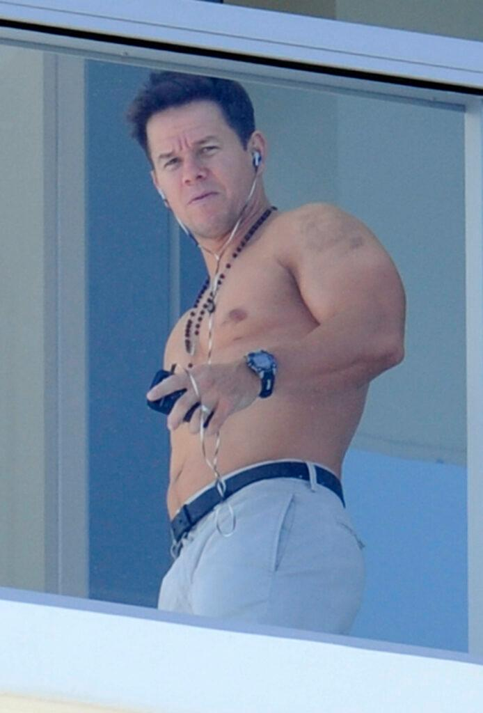 Mark Wahlberg shows off his muscles while waving shirtless from his South Beach hotel balcony
