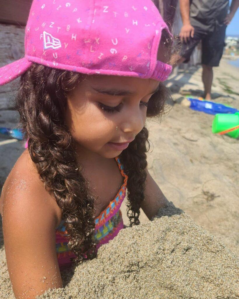 Dream Kardashian buried in the sand.
