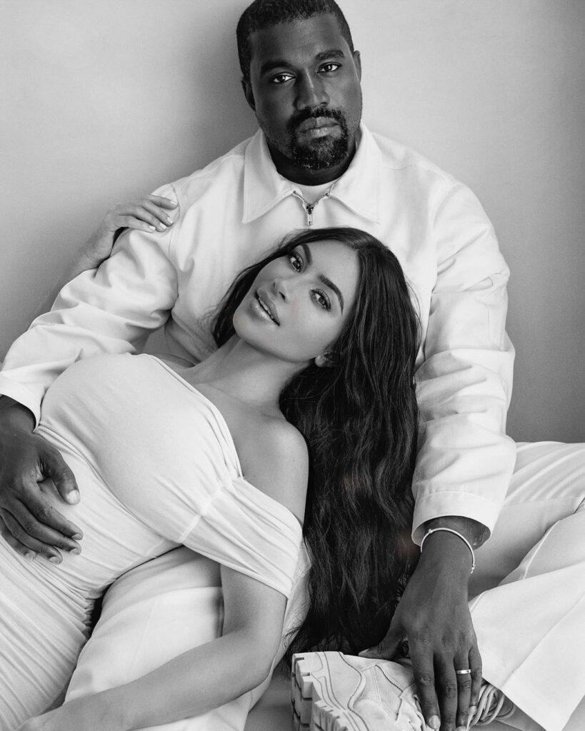 A black and white themed photo showing Kanye West and Kim Kardashian in white outfits.