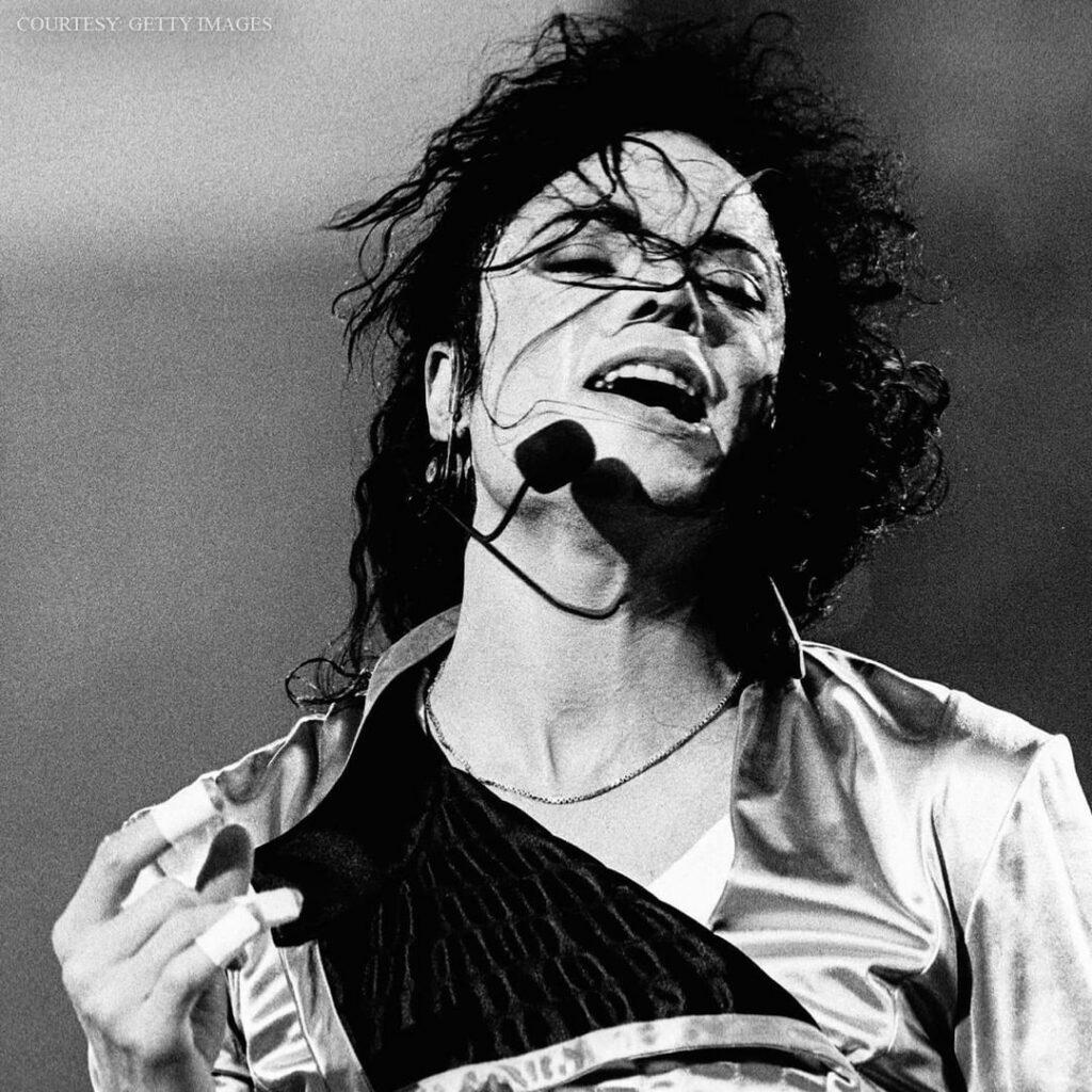 A black and white themed photo of Michael Jackson singing.