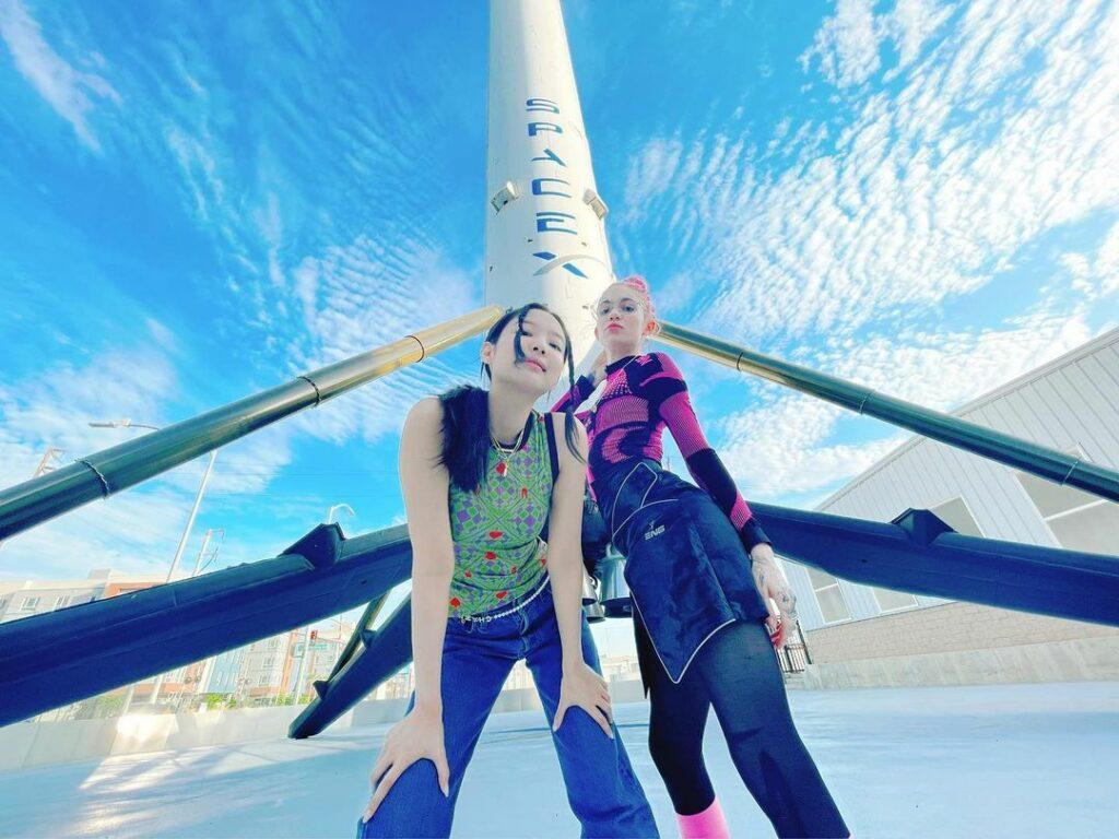 Grimes posing in front of a SpaceX rocket.