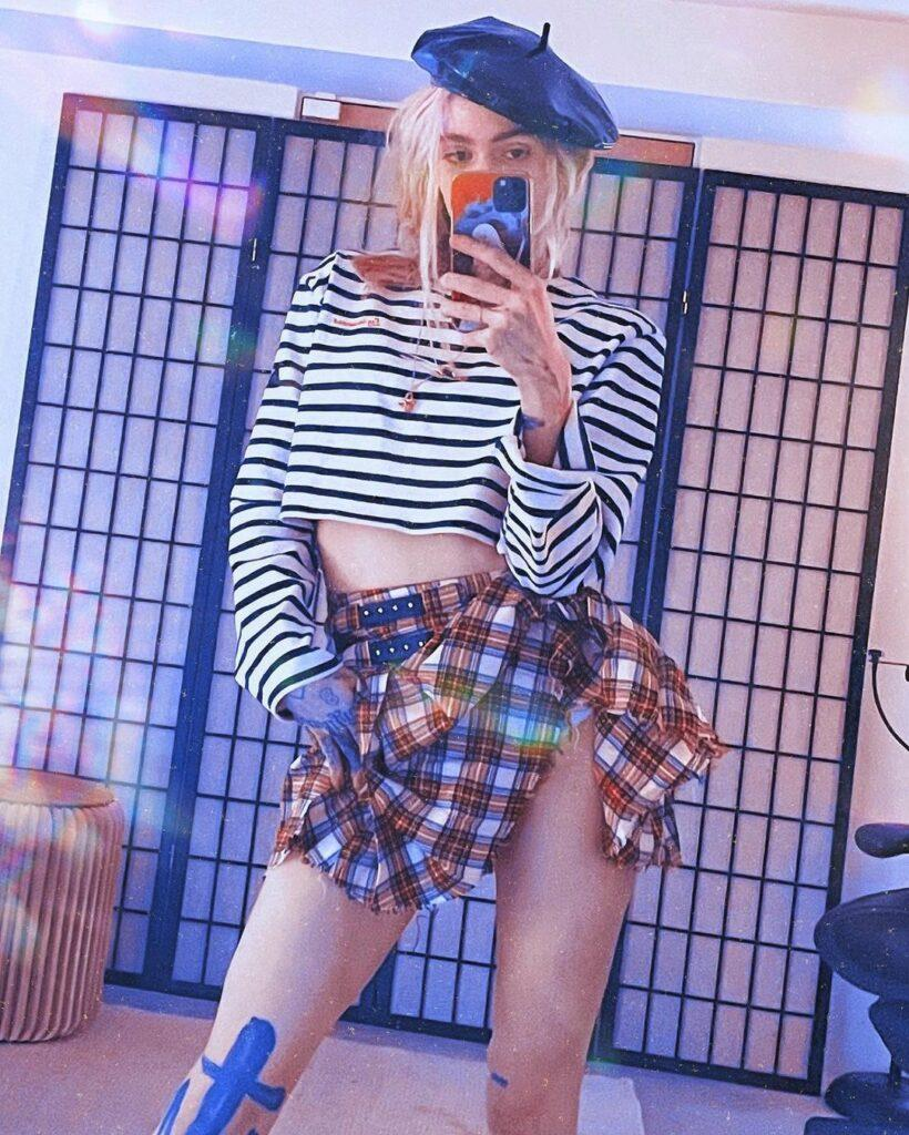 Grimes wearing a plaid skirt and striped shirt.