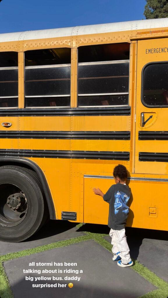 Stormi Webster touching a school bus.