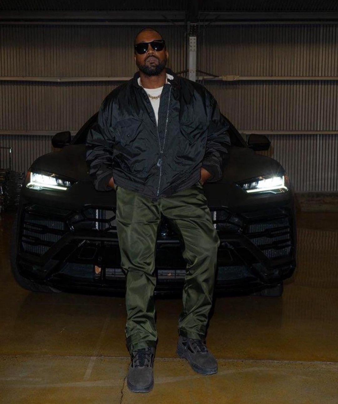 A photo showing Kanye West in a black jacket and green pant.