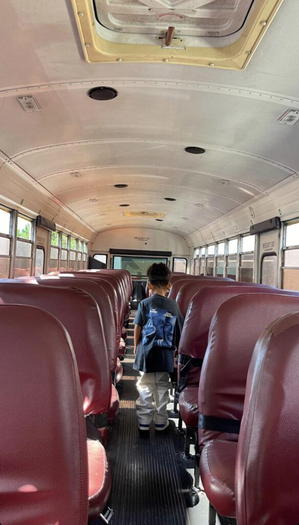 Stormi Webster standing inside an empty school bus.