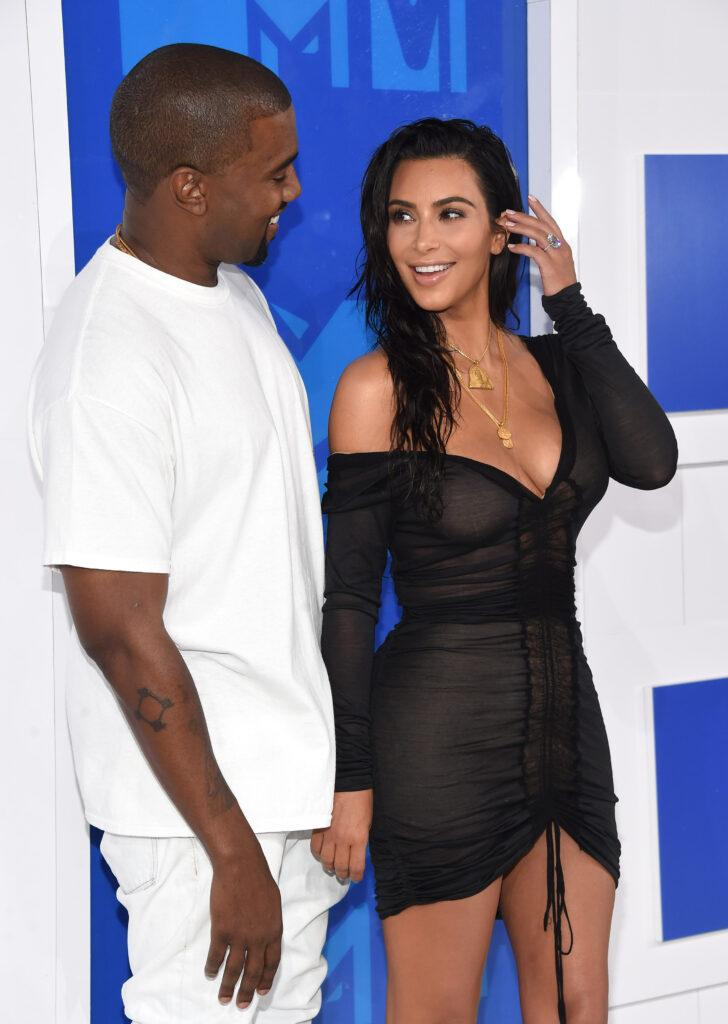 Kim Kardashian and Kanye West smiling at each other