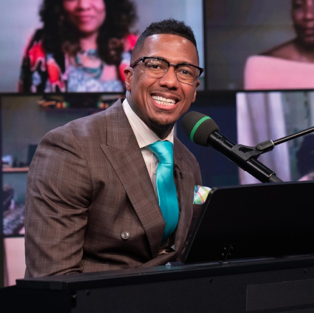 Nick Cannon smiling at a piano