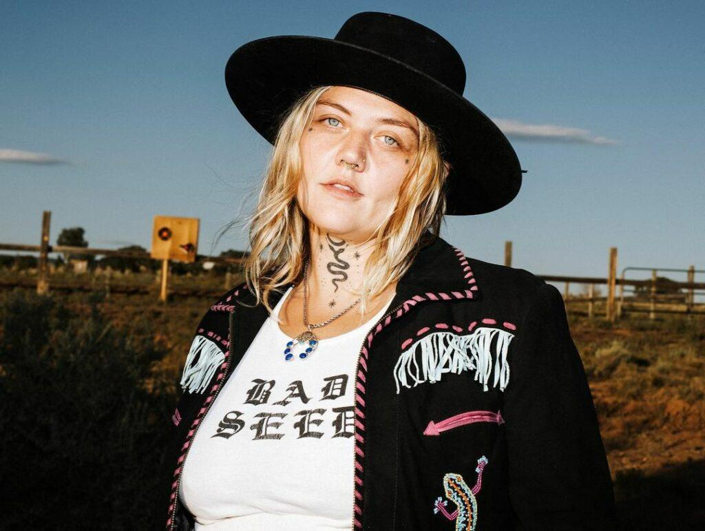 A lovely photo showing Elle King dressed in a white and black outfit with a matching hat.