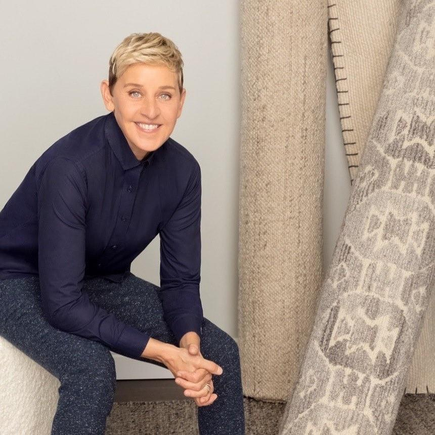 A photo of Ellen DeGeneres sporting a blue-black T-shirt and dark color denim pant.