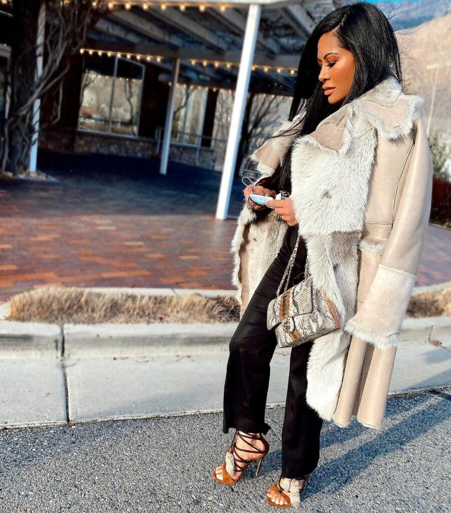 A photo of Jen Shah in fur coat paired with black pant and sandals.
