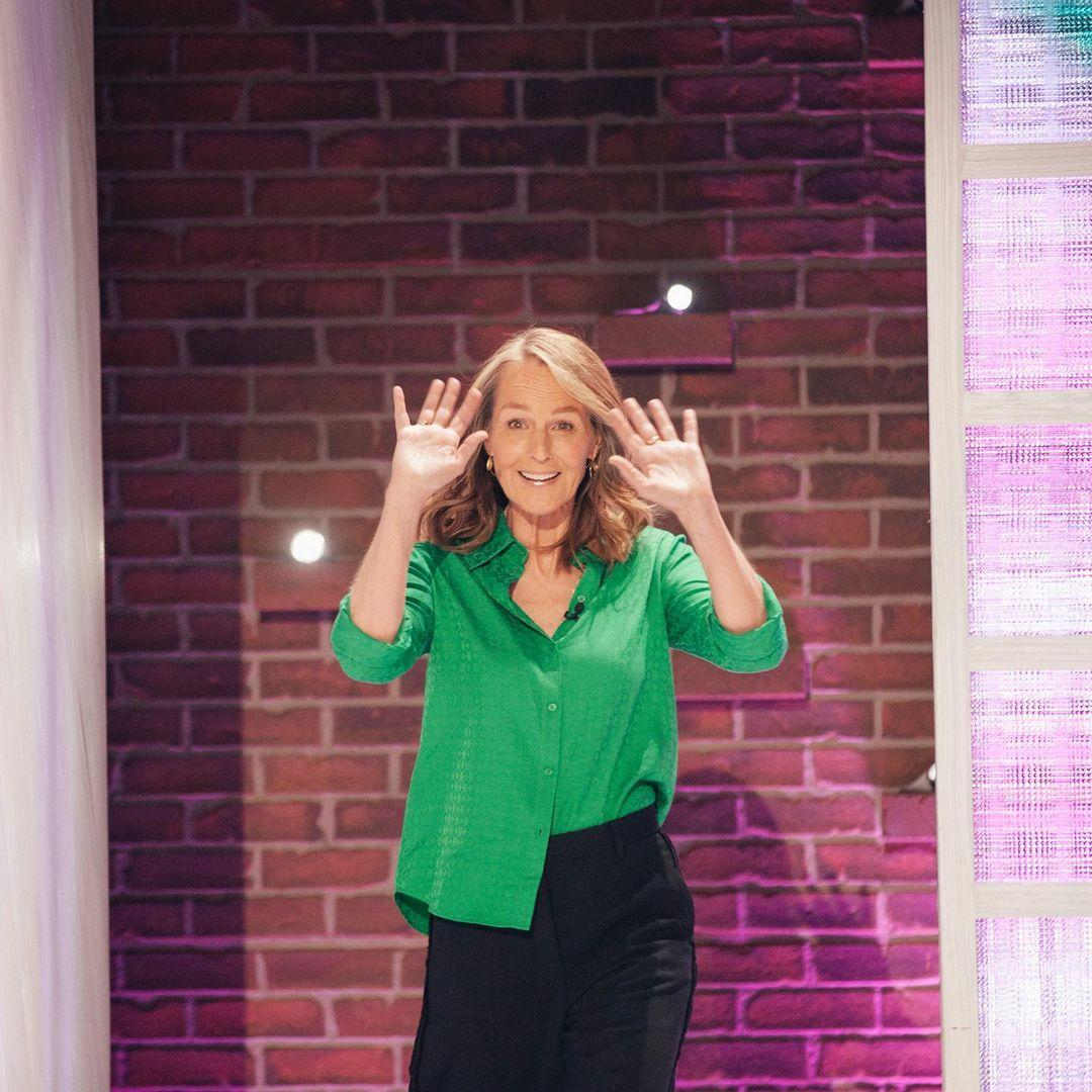 A photo of Helen Hunt in a green button-down shirt and black pant.