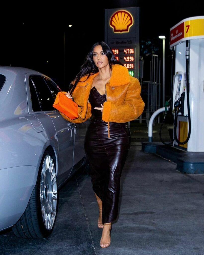 Kim Kardashian looks stunning in this black leather dress paired with a gold-yellow jacket