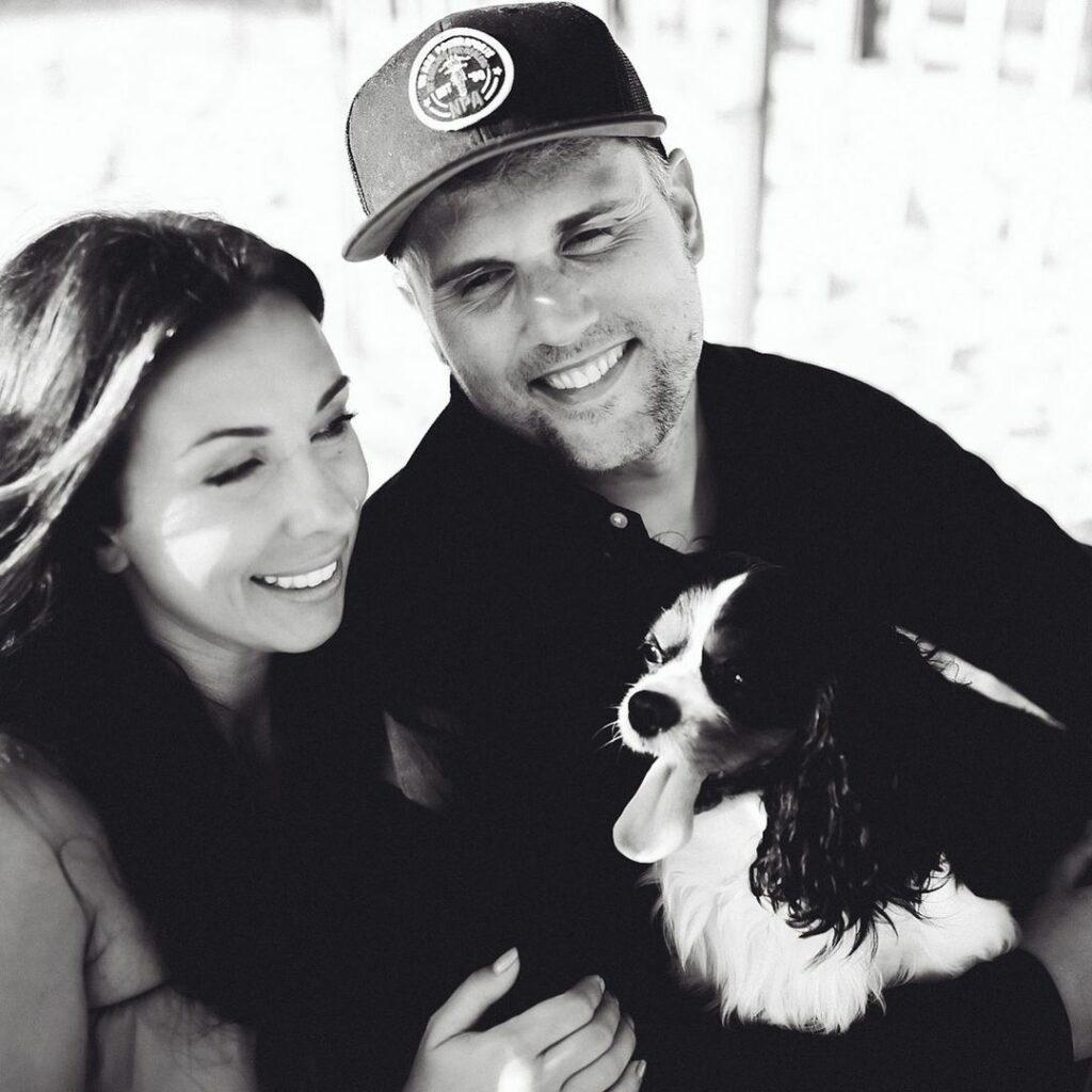 A black and white themed photo of Mackenzie, Ryan Edwards, and their dog.