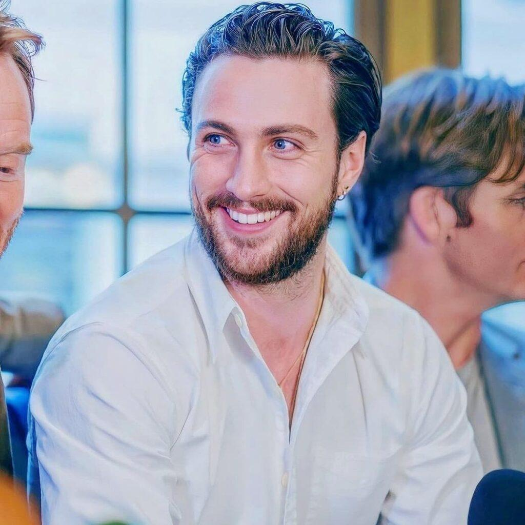 A photo of Aaron Taylor-Johnson smiling profusely at the camera in a white T-shirt