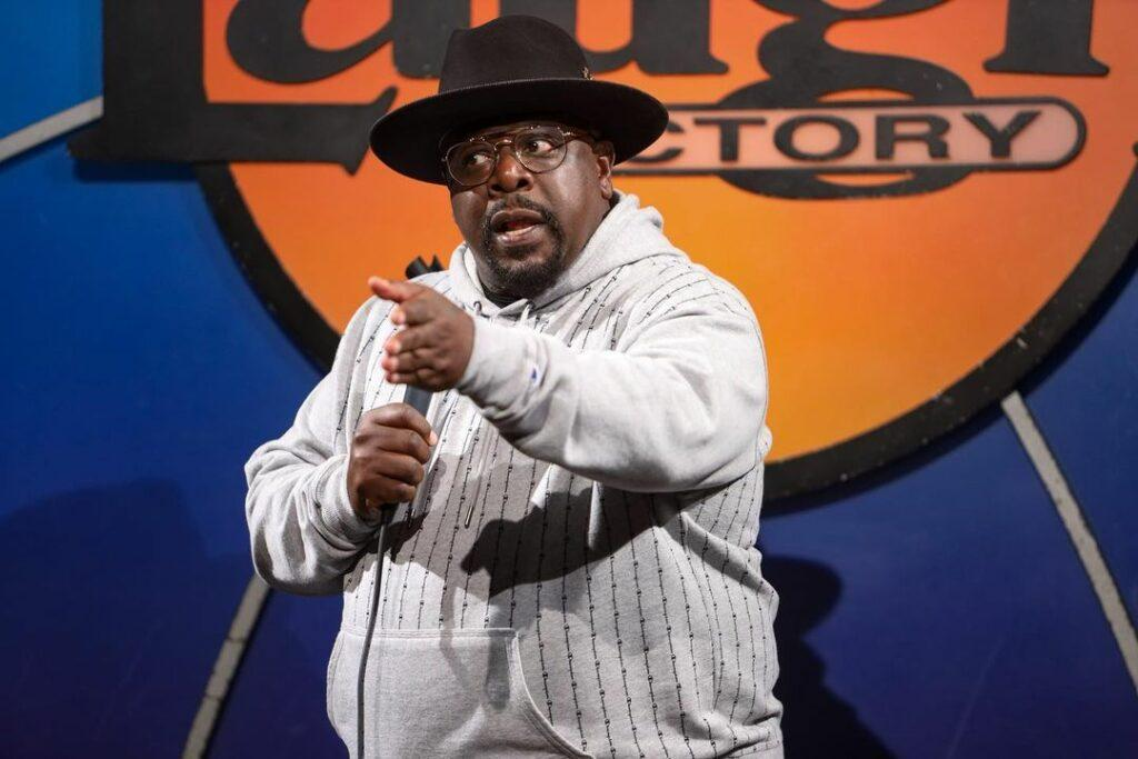 A photo showing Cedric The Entertainer sporting a gray hoodie and black hat.
