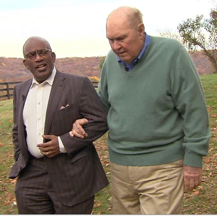 A photo of Al Roker and Willard Scott holding hands while walking on a field.