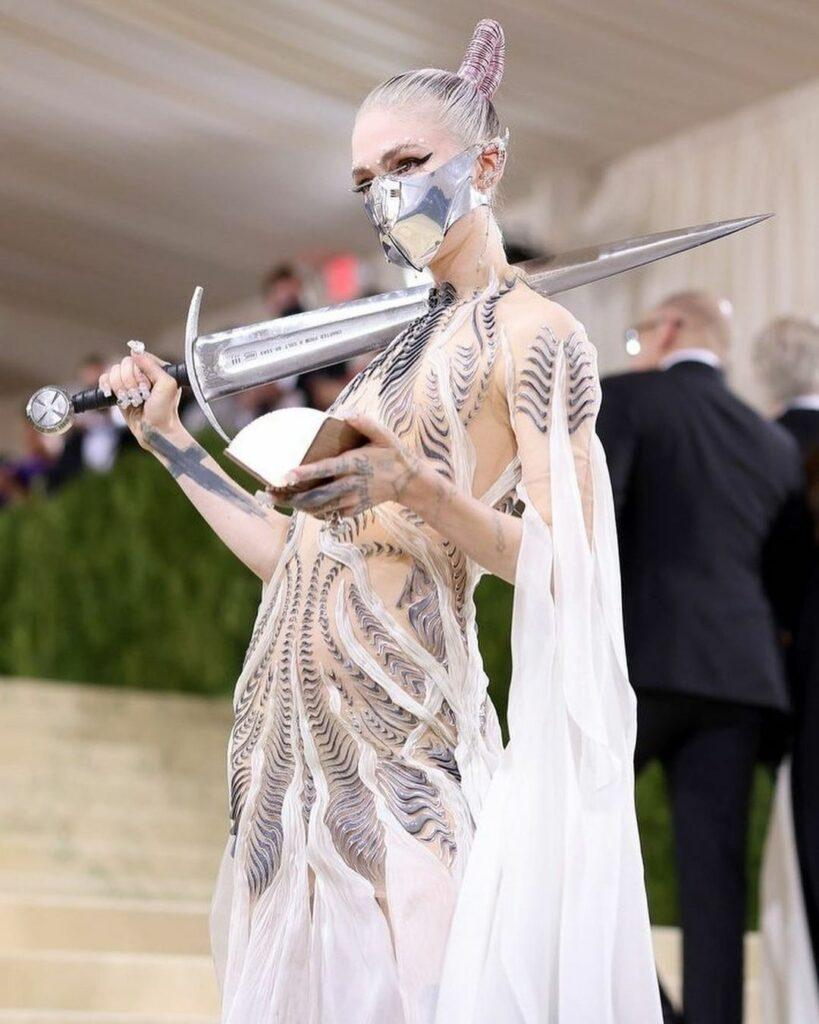 A photo showing Grimes dressed in a silver-themed dress with a shiny sword hanging over her shoulder