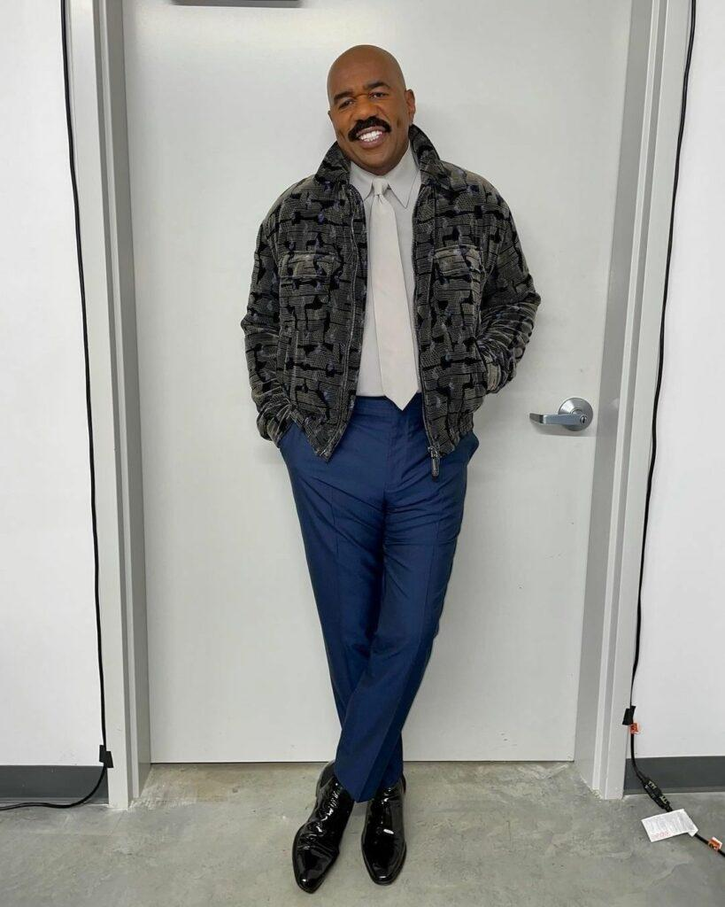 An amazing photo showing Steve Harvey in a gray jacket over a white shirt and blue pant.