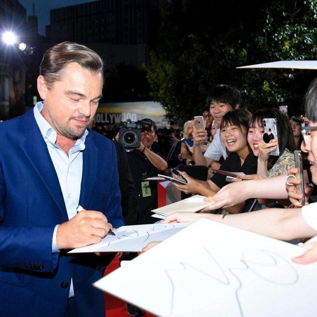 A photo of Leonardo DiCaprio signing autographs for his female fans