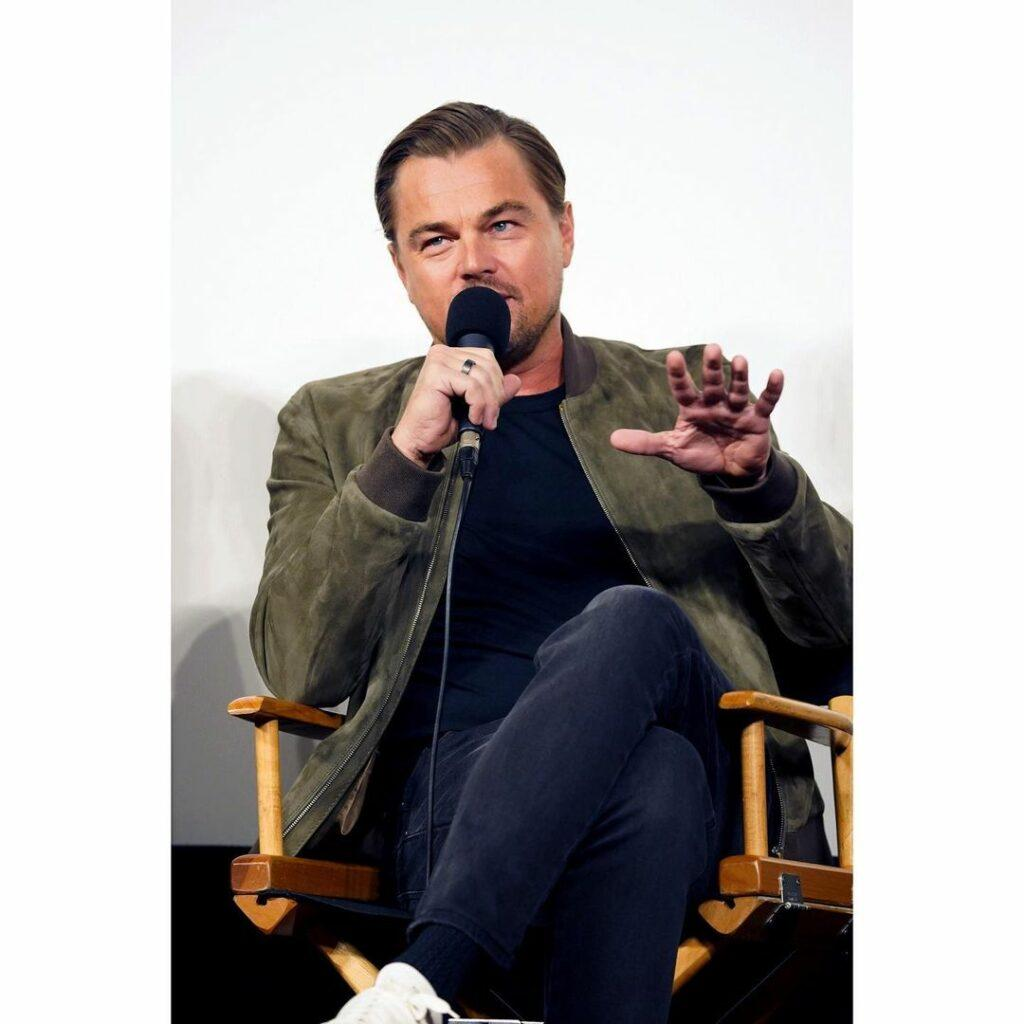 A photo showing Leonardo DiCaprio sitting and talking through a microphone