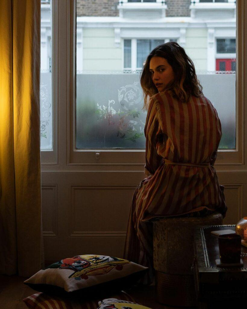 A photo showing Lily James in a brown striped robe, sitting close to the window in her bedroom.