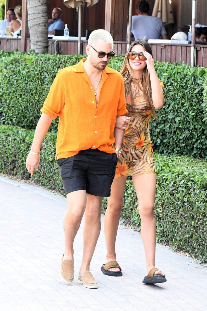 Scott Disick and girlfriend Amelia Hamlin color coordinate in orange hues as they take a stroll along the beach in Miami