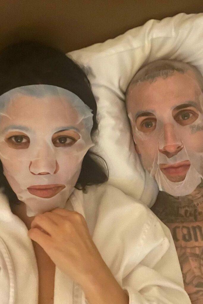 Kourtney Kardashian and Travis Barker wearing face masks