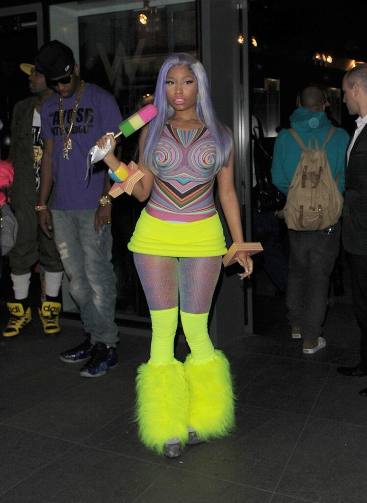 Nicki Minaj leaving the W Hotel in Leicester Square The singer showed off her new blue hair and wore a multicoloured top neon yellow hot pants tights and neon yellow boots