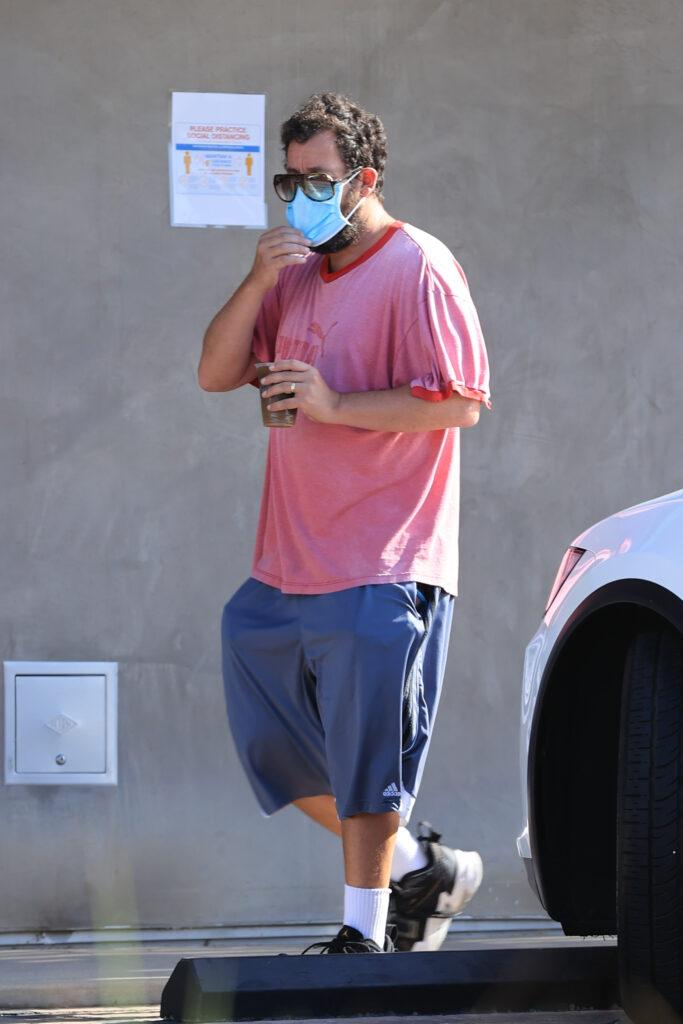 Adam Sandler struggles with sunglasses and mask combination as he grabs his morning coffee