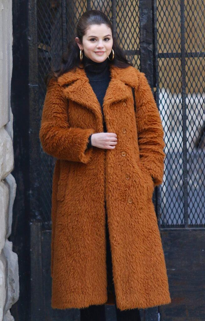 Selena Gomez is all smiles sporting a long brown orange furry coat while filming Only Murders In The Building in NYC
