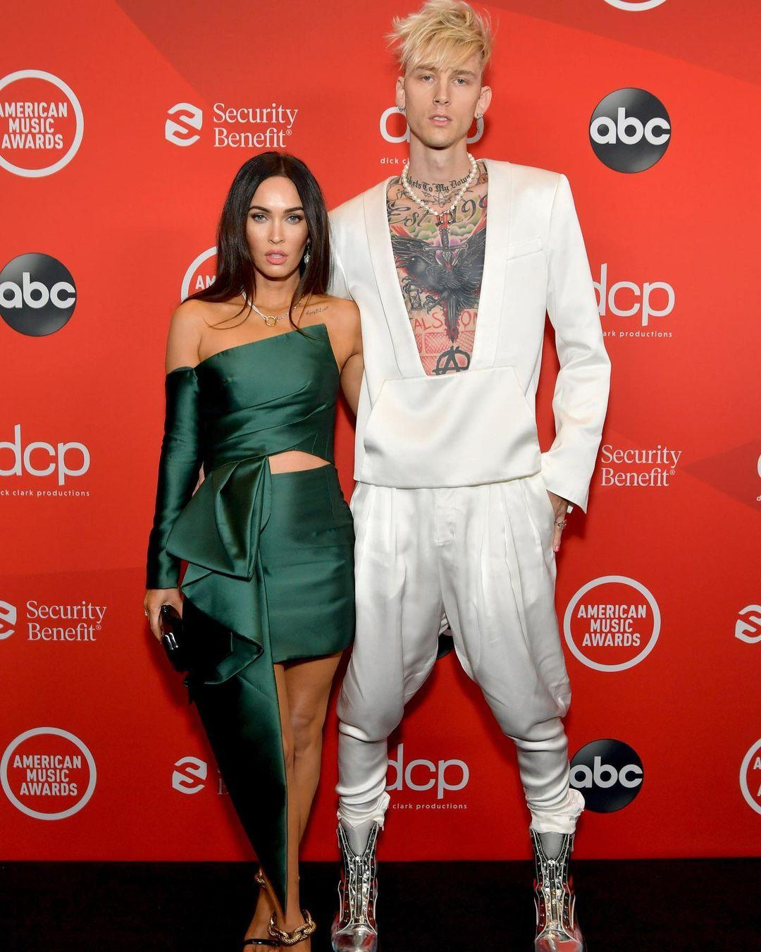 A photo of Machine Gun Kelly and Megan Fox at a red carpet adorned in a white and green color outfit respectively.