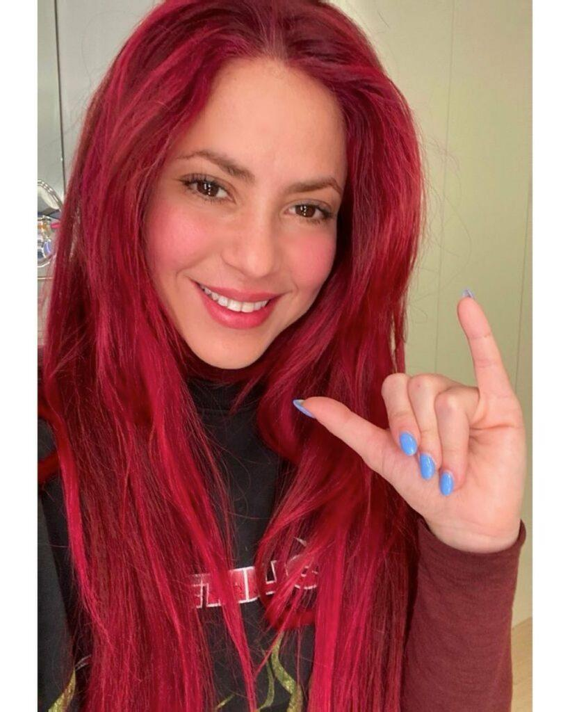 Shakira has long red hair and bright blue nails in a selfie.