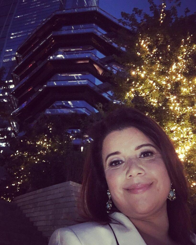 A lovely photo showing Ana Navarro out at night in front of a shiny sky-scraper behind her.
