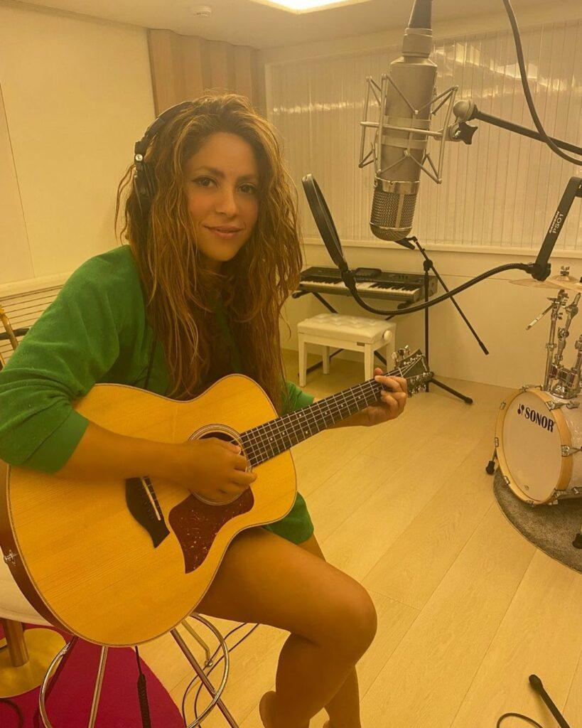 Shakira is playing acoustic guitar in a small recording studio.